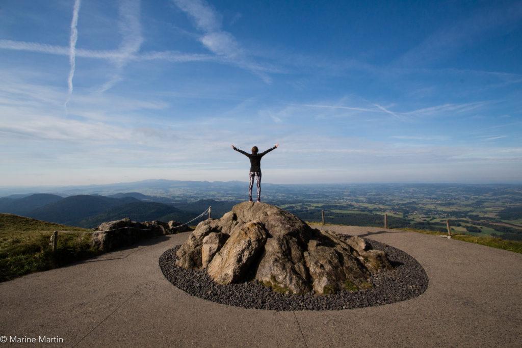 Volcans - Fille les bras écartés au sommet du Puy de Dome