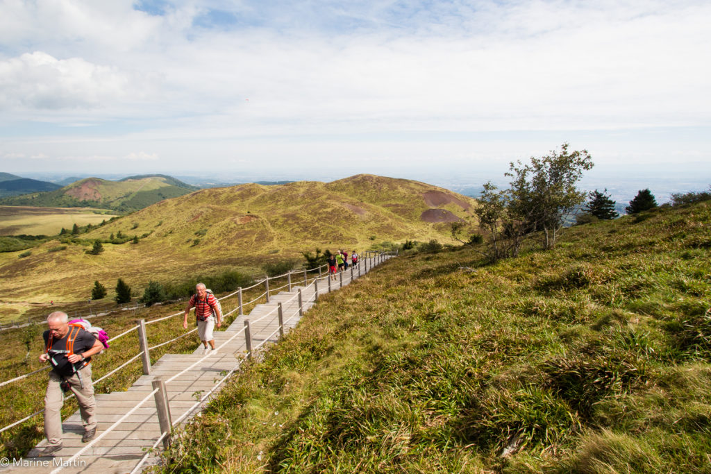 Volcans - Escaliers du sentier pour découvrir la Chaîne des Puys avec des personnes qui montent