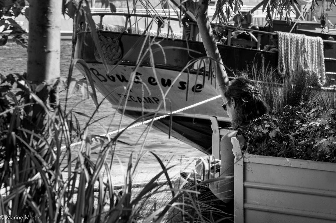 Journée à Paris : Jeune femme assise sur les quais de Seine, qui boude, près d'un bateau appelé Boudeuse
