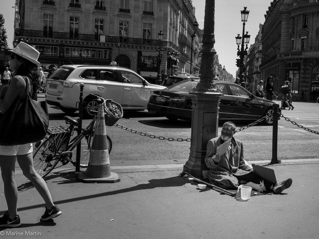 Journée à Paris : Un mendiant assis dans la rue avec un lapin, ignoré par les passants