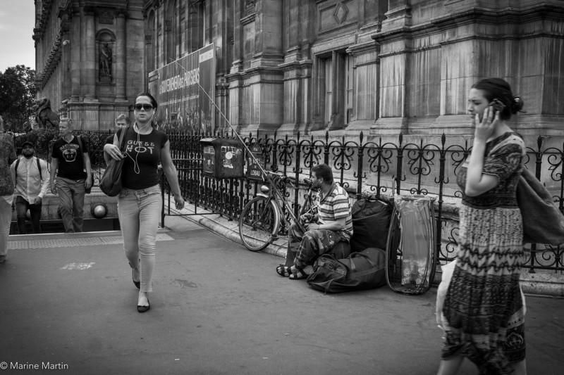 Journée à Paris : Passants parisiens ignorant un SDF qui fait la manche avec un seau pendant à une canne à pêche
