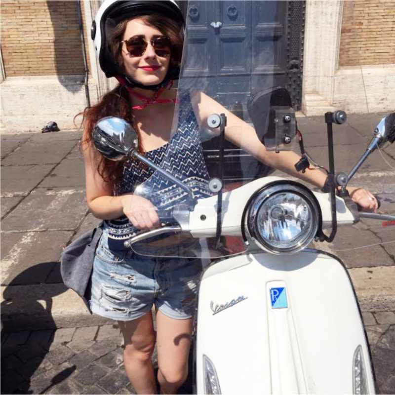 Jeune fille à côté d'une Vespa